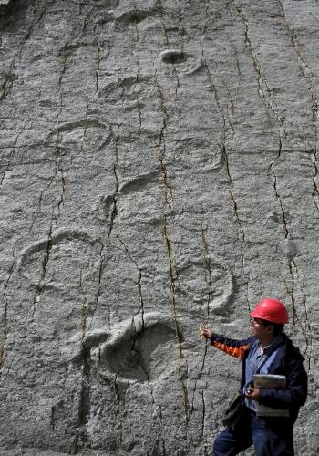 24.abr.2015 - Guia e visitante observam a formação rochosa com pegadas de dinossauros no sítio paleontológico de Cal Orcko, situado em uma pedreira em Sucre, na Bolívia. Frequentes deslizamentos de terra no sítio arqueológico têm revelado novas trilhas de dinossauros, com algumas pegadas pertencentes a novas espécies, de acordo com pesquisadores locais