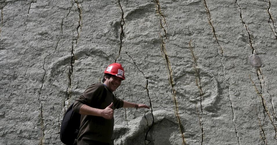 24.abr.2015 - Um visitante posa para fotos diante de pegadas de dinossauro no sítio paleontológico de Cal Orcko, localizado em uma pedreira em Sucre, na Bolívia. Frequentes deslizamentos de terra no sítio arqueológico têm revelado novas trilhas de dinossauros, com algumas pegadas pertencentes a novas espécies, de acordo com pesquisadores locai