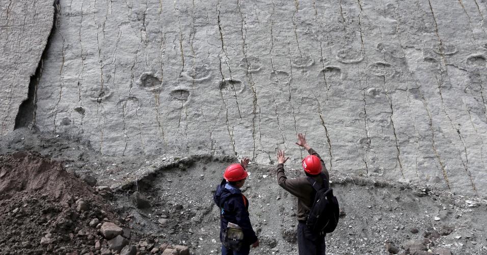 29.abr.2015 - Visitantes observam pegadas de dinossauro no sítio paleontológico de Cal Orcko, localizado em uma pedreira em Sucre, na Bolívia. Frequentes deslizamentos de terra no sítio arqueológico têm revelado novas trilhas de dinossauros, com algumas pegadas pertencentes a novas espécies, de acordo com pesquisadores locais