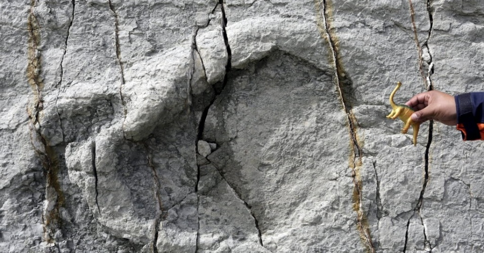 29.abr.2015 - Um guia segura uma réplica de dinossauro de brinquedo diante de uma pegada no sítio paleontológico de Cal Orcko em sucre, na Bolívia. Frequentes deslizamentos de terra no sítio arqueológico têm revelado novas trilhas de dinossauros, com algumas pegadas pertencentes a novas espécies, de acordo com pesquisadores locais