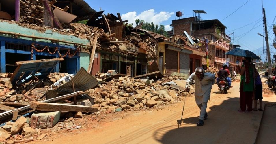 4.mai.2015 - Nepaleses passam por casas destruidas e danificadas pelo terrremoto ocorrido no sábado (25) em Nuwakot, distrito ao norte de Katmandu. Chega a 7.365 mortos e 14 mil feridos, autoridades alertam que o número final será muito maior