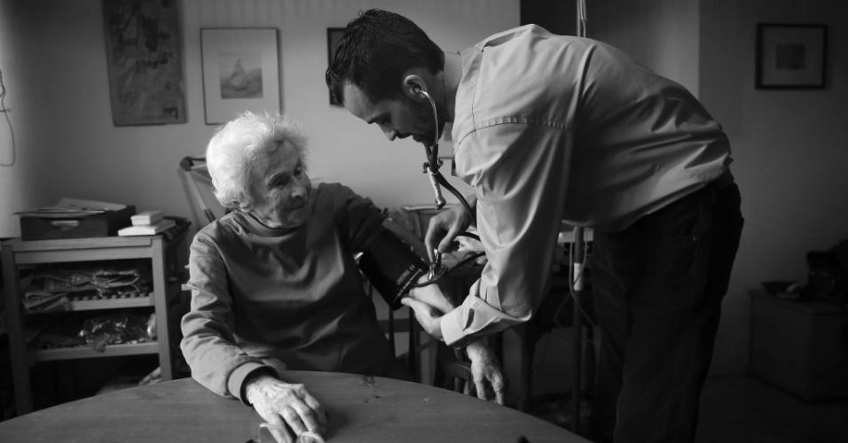 4.mai.2015 - O médico Cameron Hernandez, que integra a equipe móvel de cuidados médicos do Hospital Monte Sinai, checa a pressão arterial da paciente Naomi Replansky em seu apartamento em Nova York, nos EUA. Com a pressão para reduzir custos de internação e, ao mesmo tempo, melhorar a qualidade do serviço, uma série de sistemas hospitalares decidiram adotar uma nova abordagem: oferecer tratamento com o mesmo nível de um hospital, mas em casa. A foto foi feita em 23 de abril de 2015