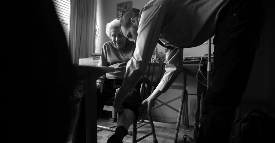4.mai.2015 - O médico Cameron Hernandez, que integra a equipe móvel de cuidados médicos do Hospital Monte Sinai, examina as pernas da paciente Naomi Replansky para ver se há sinais de inchaço, durante visita médica domiciliar em Nova York, nos EUA. Com a pressão para reduzir custos de internação e, ao mesmo tempo, melhorar a qualidade do serviço, uma série de sistemas hospitalares decidiram adotar uma nova abordagem: oferecer tratamento com o mesmo nível de um hospital, mas em casa. A foto foi feita em 23 de abril de 2015