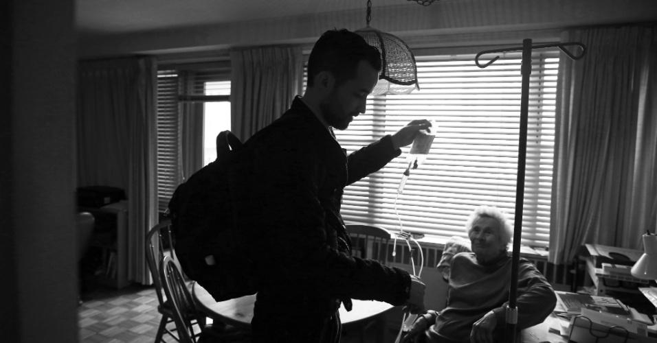 4.mai.2015 - O médico Cameron Hernandez, que integra a equipe móvel de cuidados médicos do Hospital Monte Sinai, remove equipamento de medicação intravenosa e se prepara para deixar a residência de Naomi Replansky em Nova York, nos EUA. Com a pressão para reduzir custos de internação e, ao mesmo tempo, melhorar a qualidade do serviço, uma série de sistemas hospitalares decidiram adotar uma nova abordagem: oferecer tratamento com o mesmo nível de um hospital, mas em casa. A foto foi feita em 23 de abril de 2015