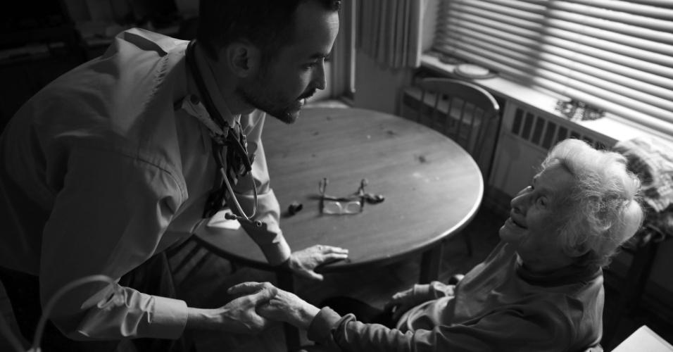 4.mai.2015 - O médico Cameron Hernandez, que integra a equipe móvel de cuidados médicos do Hospital Monte Sinai, segura a mão da paciente Naomi Replansky, durante exame médico em seu apartamento em Nova York, nos EUA. Com a pressão para reduzir custos de internação e, ao mesmo tempo, melhorar a qualidade do serviço, uma série de sistemas hospitalares decidiram adotar uma nova abordagem: oferecer tratamento com o mesmo nível de um hospital, mas em casa. A foto foi feita em 23 de abril de 2015