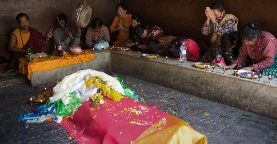 4.mai.2015 - Pessoas oram por vítima do terremoto do dia 25 no Nepal em centro de cremação em Katmandu. Os templos crematórios estão sobrecarregados para atender as famílias das mais de 7.000 vítimas do sismo