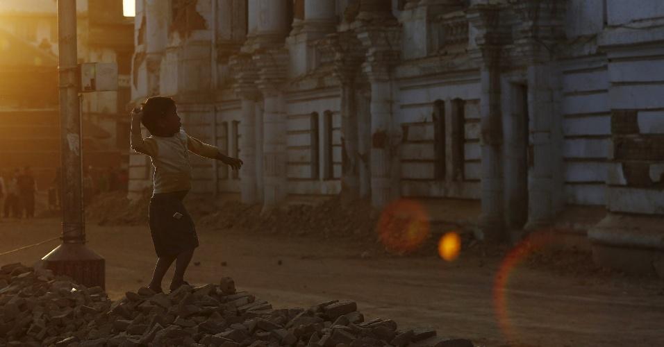 5.mai.2015 - Garoto atira pedras em prédios destruídos pelo terremoto do dia 25 em Katmandu, no Nepal