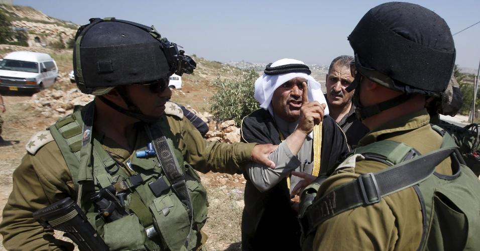 6.mai.2015 - Palestino discute com soldados israelenses na aldeia de Soba, perto da cidade de Hebron, na Cisjordânia, após ser informado pelo Exército israelense que ele e outros palestinos não têm permissão de acessar a região