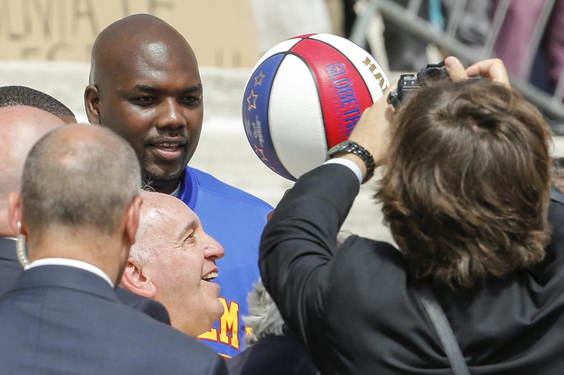 6.mai.2015 - Papa Francisco sorri enquanto joga bola de basquete de membro da equipe do Harlem Globetrotters, recebida durante a audiência semanal na Praça de São Pedro