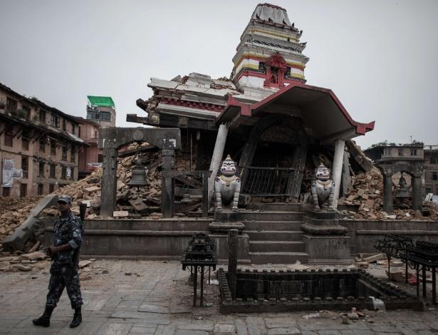 8.mai.2015 - Policial nepalês vigia templo destruído na vila de Bungamati, no subúrbio de Katmandu. 8.mai.2015 - Um policial nepalês caminha por um templo destruído na vila de Bungamati, no subúrbio de Katmandu. Um terremoto de magnitude de 7,8 atingiu o país em 25 de abril, destruindo completamente 288.798 casas em todo país, enquanto outras 254.112 residências foram parcialmente danificadas, de acordo com o comando do Centro de Operação de Emergência do Nepal