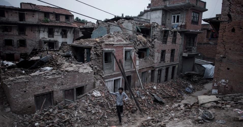 8.mai.2015 - Um morador caminha entre edifícios danificados pelo terremoto na vila de Bungamati, no subúrbio de Katmandu. Um terremoto de magnitude de 7,8 atingiu o país em 25 de abril, destruindo completamente 288.798 casas em todo país, enquanto outras 254.112 residências foram parcialmente danificadas, de acordo com o comando do Centro de Operação de Emergência do Nepal