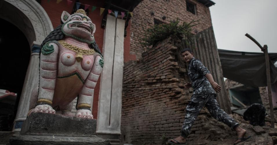 8.mai.2015 - Um policial nepalês caminha por um templo destruído na vila de Bungamati, no subúrbio de Katmandu. Um terremoto de magnitude de 7,8 atingiu o país em 25 de abril, destruindo completamente 288.798 casas em todo país, enquanto outras 254.112 residências foram parcialmente danificadas, de acordo com o comando do Centro de Operação de Emergência do Nepal