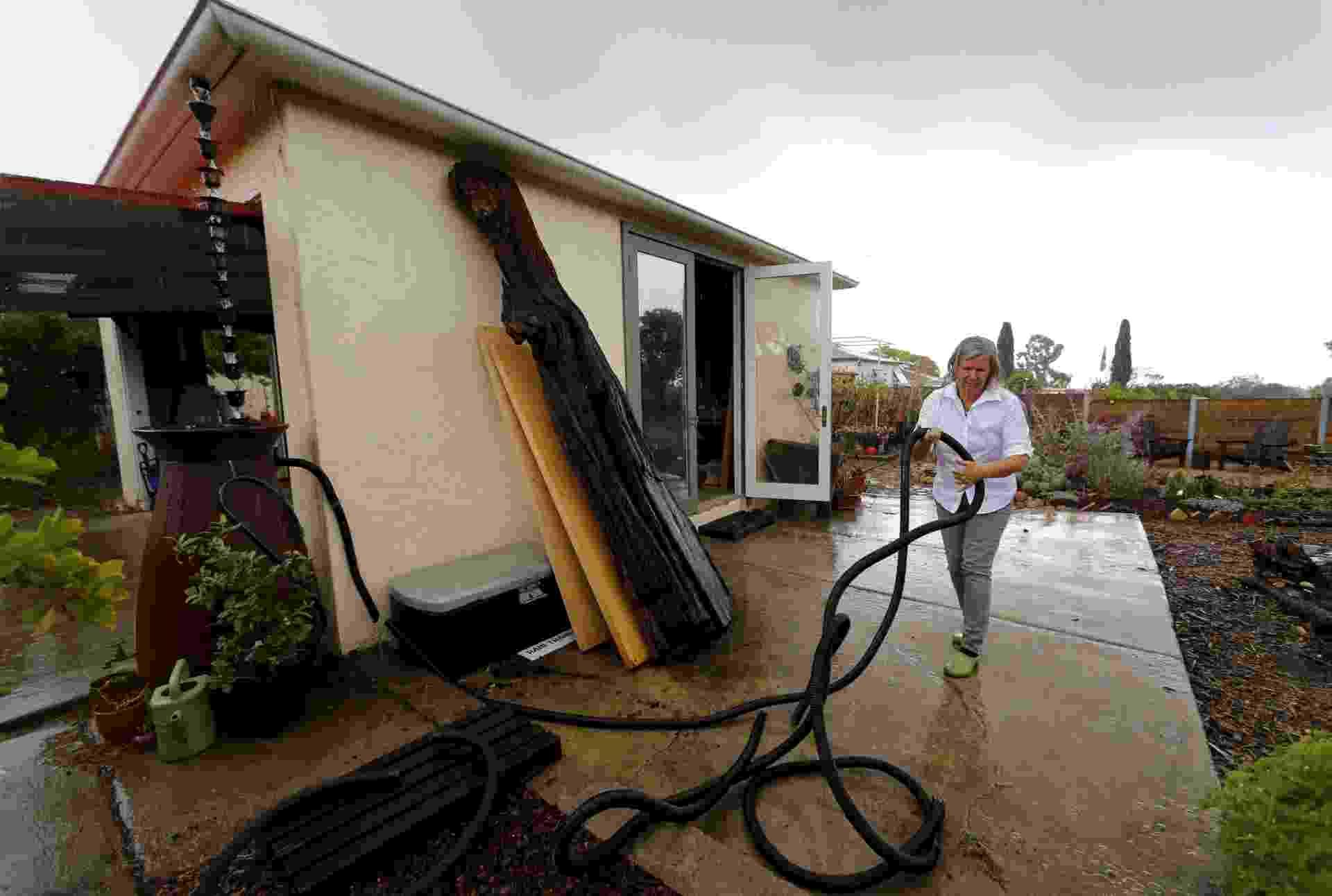 8.mai.2015 - Candace Vanderhoff criou um sistema artesanal para coleta da água e tem ajudado os californianos a lidarem com a pior seca da história do Estado norte-americano. O sistema artesanal coleta a água da chuva da calha para dentro de um galão de 65 litros, enquanto Candace Vanderhoff segura uma mangueira em seu jardim em San Diego, na Califórnia (EUA). Candece criou a RainThanks, uma empresa que oferece soluções como essa para aproveitamento de água - Mike Blake/Reuters