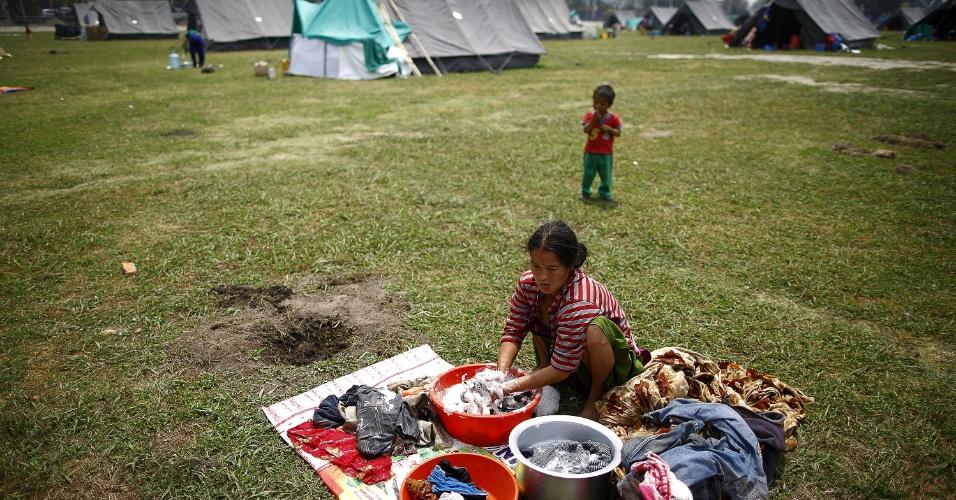 8.mai.2015 - Vítima do terremoto de 25 de abril lava roupas em campo para desabrigados improvisado em Katmandu, nesta sexta-feira. Na quinta, a ONU reclamou que Dos U$ 415 milhões aos países membros e parceiros na semana passada, somente 22,4 milhões foram fornecidos para auxiliar as vítimas da tragédia que matou mais de 7.500 pessoas no Nepal