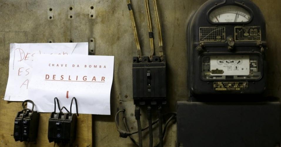 """9.mai.2015 - """"Chave da bomba: Desligar"""", informa cartaz deixado ao lado de interruptores no abrigo antiaéreo do edifício Tupynambás, no centro de Belo Horizonte (MG). Inaugurado em 1943, o local fica no subsolo do prédio, três metros abaixo da portaria, e tem ventilação e comunicação exterior. Ele está abandonado, com paredes mofadas e lodo no piso, e funciona como um quarto de despejo. Difícil imaginar que há 70 anos ser """"dotado de abrigo antiaéreo"""" funcionava como atrativo para os lançamentos imobiliários. Na década de 1940, o mundo vivenciava a Segunda Guerra Mundial, e o Brasil havia declarado guerra aos países do Eixo (Alemanha, Itália e Japão)"""