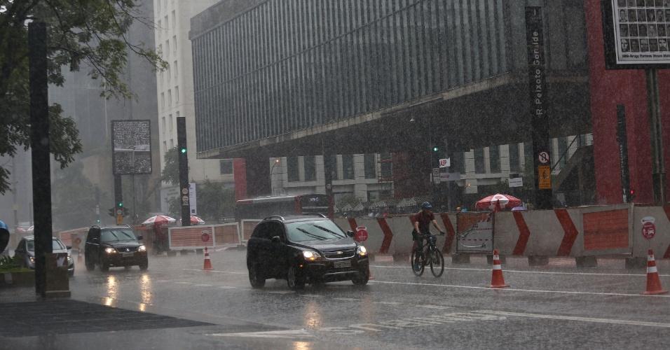 10.mai.2015 - Pedestres se protegem da chuva na avenida Paulista, em São Paulo, neste domingo (10).