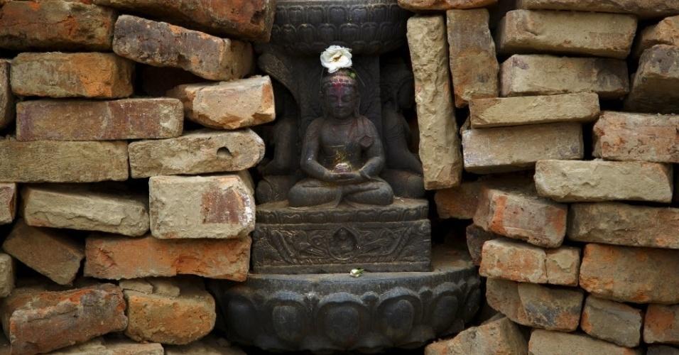 11.mai.2015 - Estátua do Buda permanece intacta entre tijolos do templo Bungamati, que entrou em colapso após o terremoto de 25 de abril na vila Bungamati, em Lalitpur, no Nepal