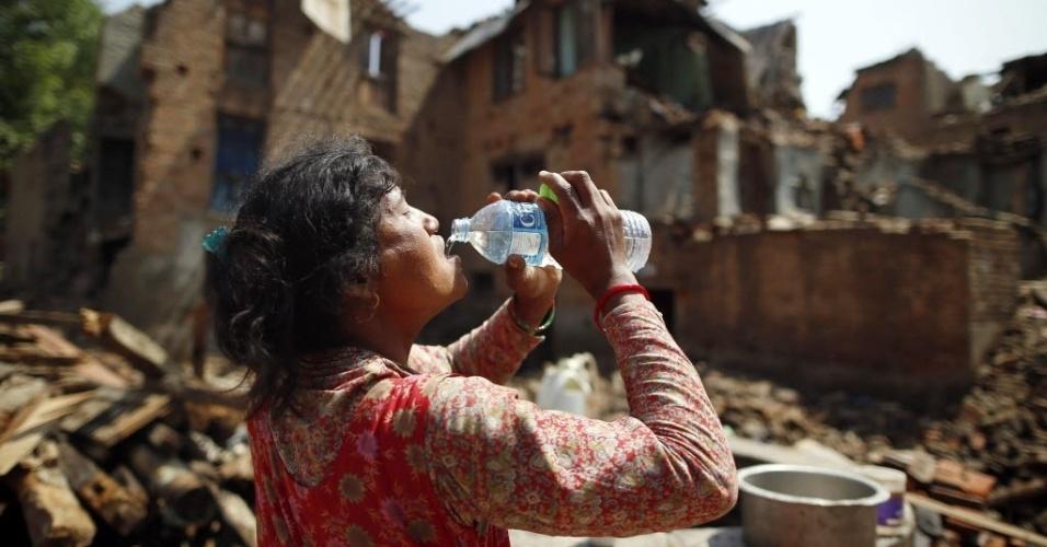 11.mai.2015 - Nepalesa bebe a água em uma área devastada de Sankhu. Várias avalanches ocorridas nos últimos dias no vale Langtang forçaram a interrupção das buscas de 300 pessoas desaparecidas desde o terremoto de 25 de abril e a retirada imediata de dezenas de cidadãos da área
