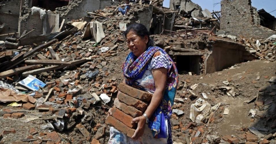 11.mai.2015 - Nepalesa recupera tijolos das ruínas em Sankhu. Várias avalanches ocorridas nos últimos dias no vale Langtang forçaram a interrupção das buscas de 300 pessoas desaparecidas desde o terremoto de 25 de abril e a retirada imediata de dezenas de cidadãos da área