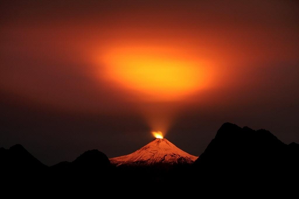 11.mai.2015 - O vulcão Villarrica ilumina o céu da cidade de Pucon, no Chile