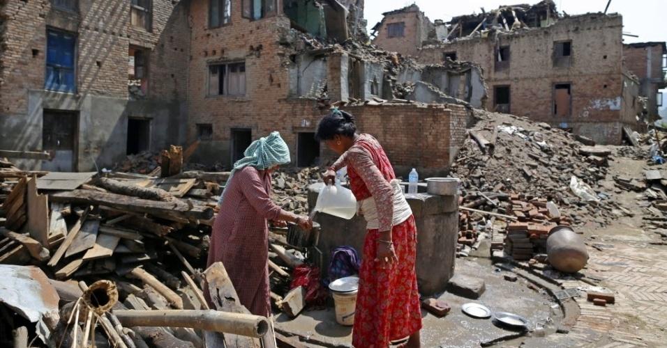 11.mai.2015 - Sobreviventes do terremoto de 25 de abril enchem recipientes com água de um poço em Sankhu, no Nepal. Várias avalanches ocorridas nos últimos dias no vale Langtang forçaram a interrupção das buscas de 300 pessoas desaparecidas e a retirada imediata de dezenas de cidadãos da área
