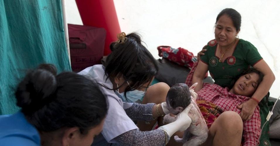 12.mai.2015 - Maya Tamang, 20, dá à luz em um abrigo improvisado do lado de fora do hospital após novo terremoto atingir o Nepal, em Bhaktapur. O sismo de magnitude 7,3 deixou mortos e feridos