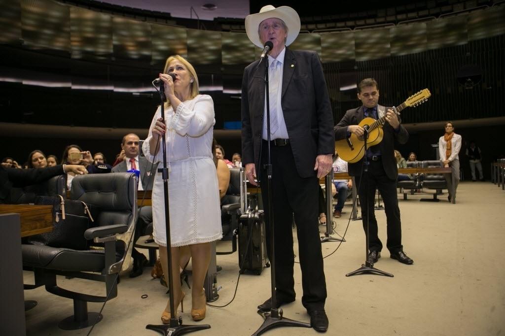12.mai.2015 - O cantor e deputado Sergio Reis (PRB-SP), ao lado de sua mulher, Ângela Marcia, cantou as músicas Tocando em Frente e Panela Velha durante sessão solene no Plenário da Câmara, em Brasília, em homenagem ao Dia Mundial da Voz