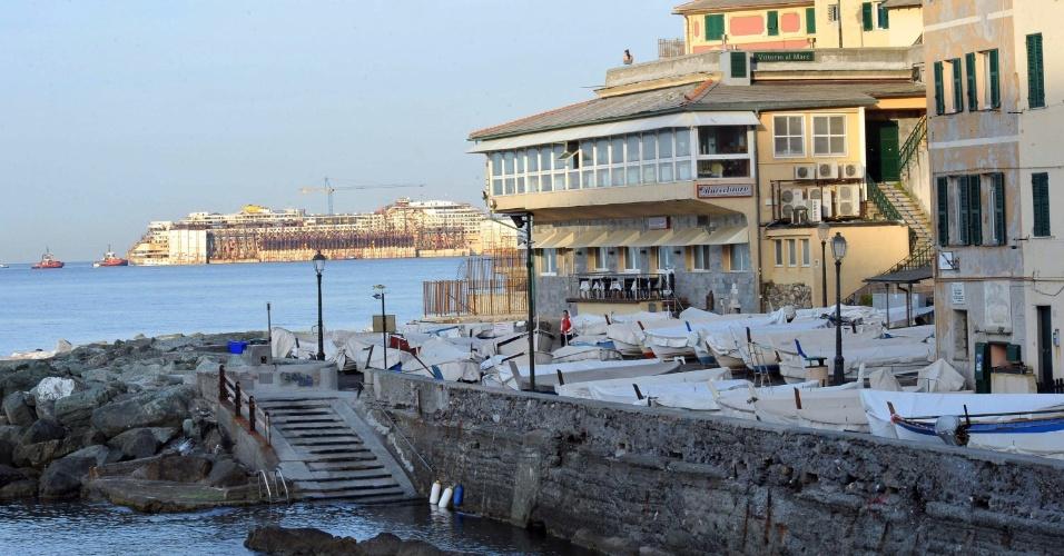 12.mai.2015 - O cruzeiro Costa Concordia aparece ao fundo do porto de Gênova, na Itália, nesta terça-feira (12). A embarcação foi removida para outro porto próximo, para ser desmontada completamente. A operação foi iniciada na segunda-feira (11). O Costa Concordia encalhou em janeiro de 2012 próximo a ilha italiano de Giglio, causando a morte de 32 pessoas