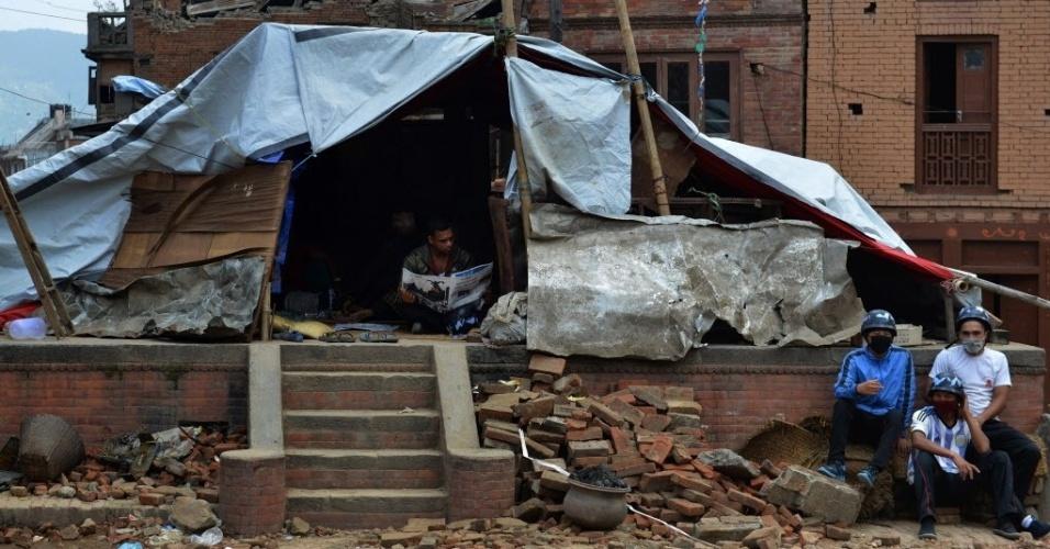 13.mai.2015 - Nepalês lê um jornal dentro de um abrigo improvisado em Bhaktapur, nos arredores de Katmandu, no Nepal. O novo sismo de magnitude 7,3 que atingiu o país em 12 de maio deixou mortos e feridos