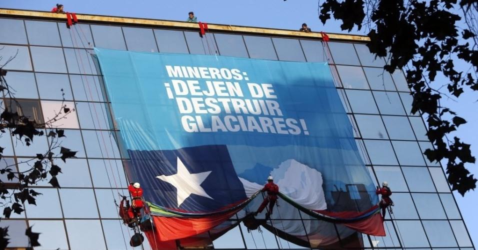 14.mai.2015 - Ativistas do Greenpeace escalam um prédio e penduram uma bandeira em protesto contra a destruição das geleiras pela mineração, em uma das principais avenidas de Santiago, no Chile