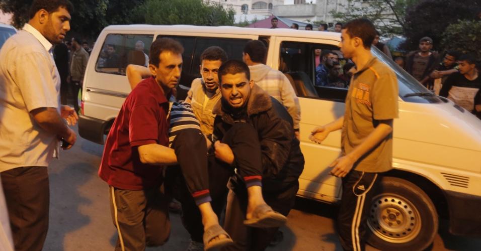 14.mai.2015 - Palestinos carregam homem ferido na entrada de um hospital no norte de faixa de Gaza, na ciidade de Beit Lahia, nesta quinta-feira (14), após uma explosão dentro de um campo de treinamento das brigadas de Ezzedine al-Qassam, braço armado do Hamas. Ao menos 50 pessoas ficaram feridas com a explosão