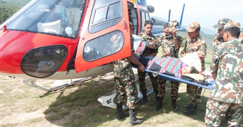 14.mai.2015 - Soldados carregam vítima de terremoto para dentro de um helicóptero no distrito de Dolakha, a 130 km de Katmandu, no Nepal, nesta quinta-feira (14). O balanço de vítimas do terremoto de terça-feira (12) no Nepal chegou a 96 mortos, anunciaram as autoridades, que ainda procuram um helicóptero americano que desapareceu com oito pessoas a bordo quando realizava tarefas de resgate