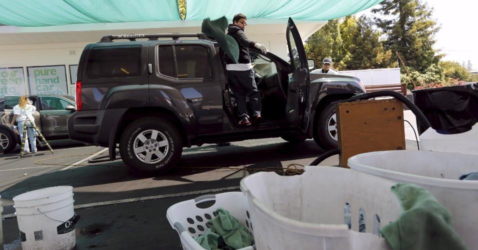 Um trabalhador descarta toalha durante a limpeza de um automóvel em Redwood City, Califórnia. A lavagem do carro não usa mangueiras, mas cerca de um copo de água, misturada com uma fórmula biodegradável é necessária para cada limpar