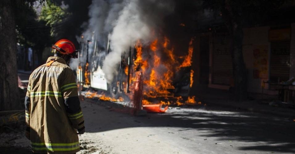 15.mai.2015 - Bombeiro trabalha no combate de um incêndio que atinge um ônibus durante protesto contra a morte de dois moradores da comunidade do São Carlos, no Estácio, na zona norte do Rio de Janeiro (Brasil). Desde o dia 8 de maio, pelo menos dez pessoas foram mortas em uma guerra de facções na região