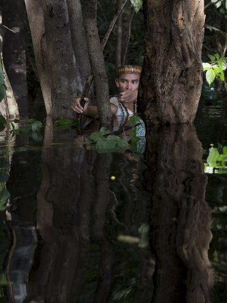 15.mai.2015 - Dream Braga, 18, índio da tribo cambeba, mira com arco e flecha dentro de um rio próximo à aldeia Três Unidos - Bruno Kelly/Reuters
