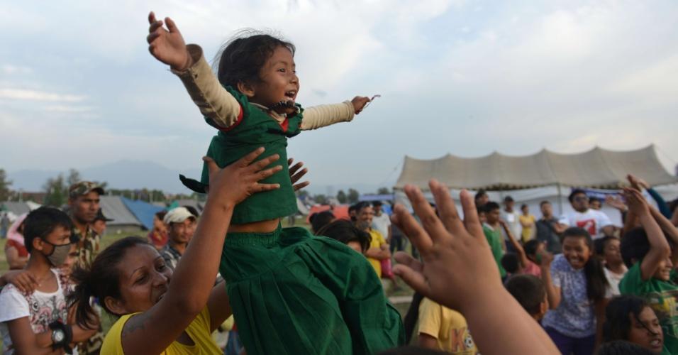 15.mai.2015 - Mãe e filha participam de uma sessão de ioga do riso para ajudar a aliviar o trauma entre os sobreviventes de dois terremotos que destruíram grande parte do país em três semanas, em Katmandu, Nepal. Um novo tremor de magnitude 7,3 atingiu o país em 12 de maio, deixando mortos e feridos