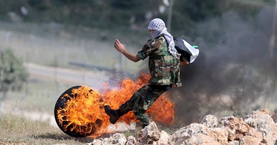 15.mai.2015 - Manifestante chuta um pneu em chamas durante confronto com tropas israelenses, após manifestação que marcou o Nakba, ou Catástrofe (dia que lembra a diáspora causada pela criação do Estado de Israel), próximo à prisão israelense de Ofer, em Ramallah, na Cisjordânia, nesta sexta-feira (15). O Nakba lembra a expulsão de mais de 700 mil palestinos após a criação de Israel, em 1948