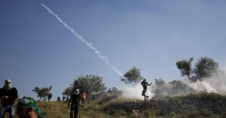 15.mai.2015 - Manifestante lança de volta uma bomba de gás em direção a tropas israelenses durante confronto após manifestação que marcou o Nakba, ou Catástrofe (dia que lembra a diáspora causada pela criação do Estado de Israel), próximo à prisão israelense de Ofer, em Ramallah, na Cisjordânia, nesta sexta-feira (15). O Nakba lembra a expulsão de mais de 700 mil palestinos após a criação de Israel, em 1948