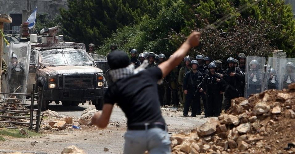 15.mai.2015 - Manifestante palestino atira pedra em direção as forças israelenses durante confrontos na aldeia de Kfar Qaddum, perto de Nablus, na Cisjordânia ocupada
