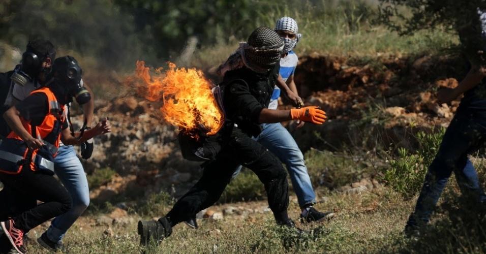 15.mai.2015 - Manifestante pega fogo após tentar acender um coquetel molotov durante confronto após manifestação que marcou o Nakba, ou Catástrofe (dia que lembra a diáspora causada pela criação do Estado de Israel), próximo à prisão israelense de Ofer, em Ramallah, na Cisjordânia, nesta sexta-feira (15). O Nakba lembra a expulsão de mais de 700 mil palestinos após a criação de Israel, em 1948