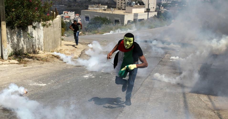 15.mai.2015 - Manifestantes palestinos fogem de bombas de gás lançadas pela polícia israelense durante confronto que se seguiu a manifestação que marcou o Nakba, ou Catástrofe (dia que lembra a diáspora causada pela criação do Estado de Israel), próximo à prisão israelense de Ofer, em Ramallah, na Cisjordânia, nesta sexta-feira (15). O Nakba lembra a expulsão de mais de 700 mil palestinos após a criação de Israel, em 1948