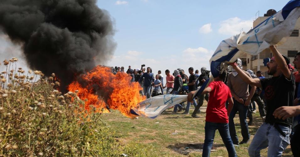 15.mai.2015 - Manifestantes queimam uma bandeira israelense durante confronto após manifestação que marcou o Nakba, ou Catástrofe (dia que lembra a diáspora causada pela criação do Estado de Israel), próximo à prisão israelense de Ofer, em Ramallah, na Cisjordânia, nesta sexta-feira (15). O Nakba lembra a expulsão de mais de 700 mil palestinos após a criação de Israel, em 1948