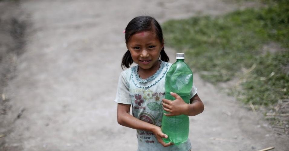15.mai.2015 - Menina carrega água potável em garrafa plástica, em Bhaktapur (Nepal). Um novo tremor de magnitude 7,3 atingiu o país em 12 de maio, deixando mortos e feridos