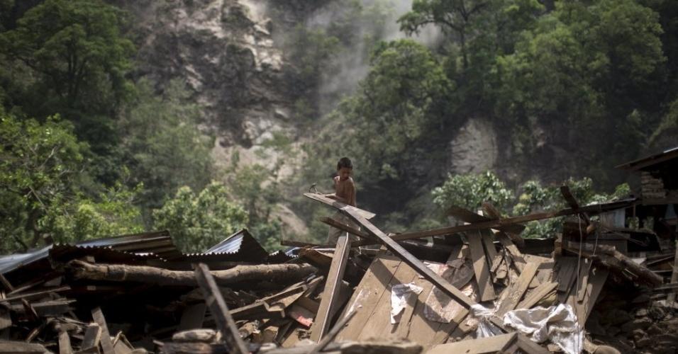 15.mai.2015 - Menino recupera madeira de sua casa que ficou destruída após um deslizamento na vila de Singati, em Dolakha, no Nepal