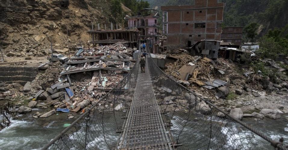 15.mai.2015 - Moradores caminham sobre uma ponte parcialmente danificada após o terremoto de magnitude 7,3 que atingiu o Nepal em 12 de maio, na vila de Singati, em Dolakha
