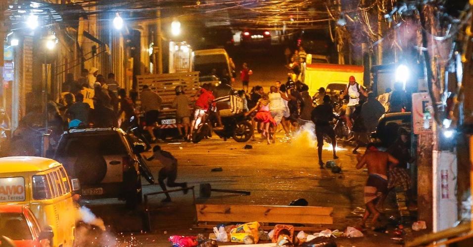 15.mai.2015 - Moradores do morro do São Carlos, localizado na cidade do Rio de Janeiro, voltaram a protestar na noite desta sexta-feira (15) por causa da morte de dois homens na comunidade. Policiais militares acompanharam o ato e houve confronto. Atacados com pedras e outros objetos, os PMs reagiram lançando bombas de gás. Moradores chegaram a fazer barricadas com sacos de lixo para tentar impedir o avanço dos policiais rumo ao alto do morro