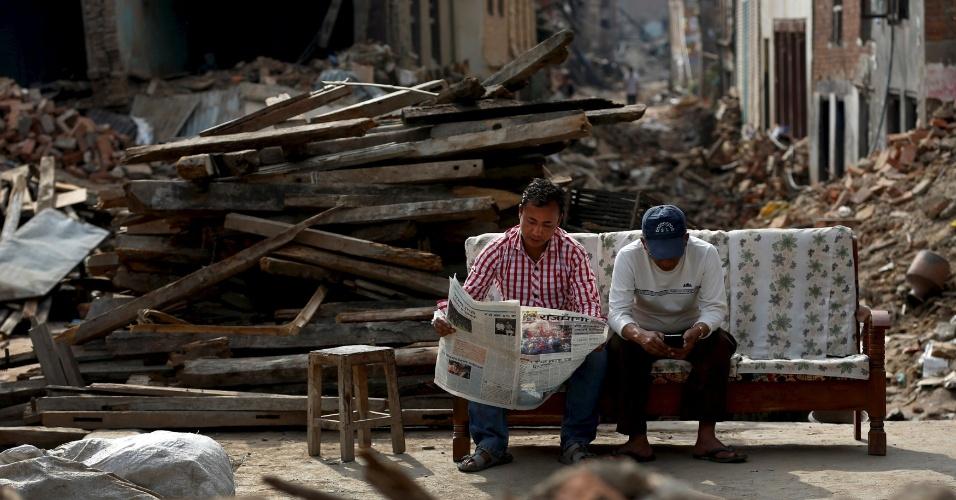 15.mai.2015 - Nepalês lê jornal enquanto amigo checa seu telefone celular, ambos sentados em meio a construções em escombros nos arredores de Katmandu, nesta sexta-feira (15), após dois grandes terremotos atingirem o país em duas semanas, deixando milhares de mortos