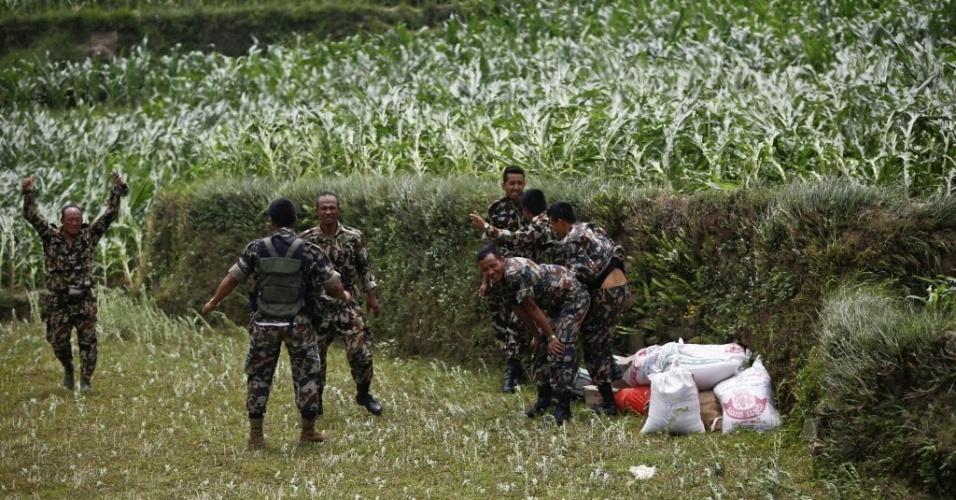 15.mai.2015 - Soldados nepaleses comemoram a chegada de um helicóptero indiano carregado com comida, na aldeia de Hagam, no distrito de Sindhupalchwok. Um novo sismo de magnitude 7,3 atingiu o país em 12 de maio, deixando mortos e feridos