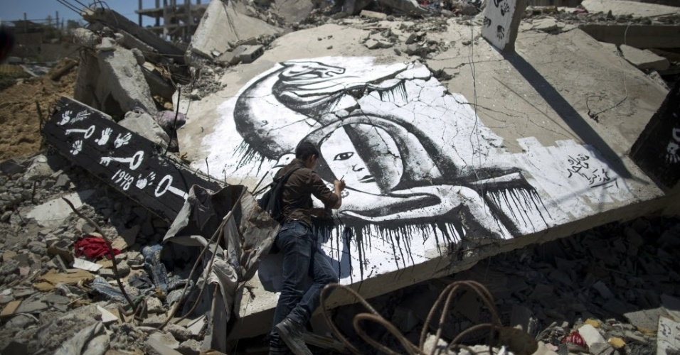 16.mai.2015 - Artista palestino desenha um mural sobre os escombros de um edifício após uma marcha para marcar o 67º aniversário da