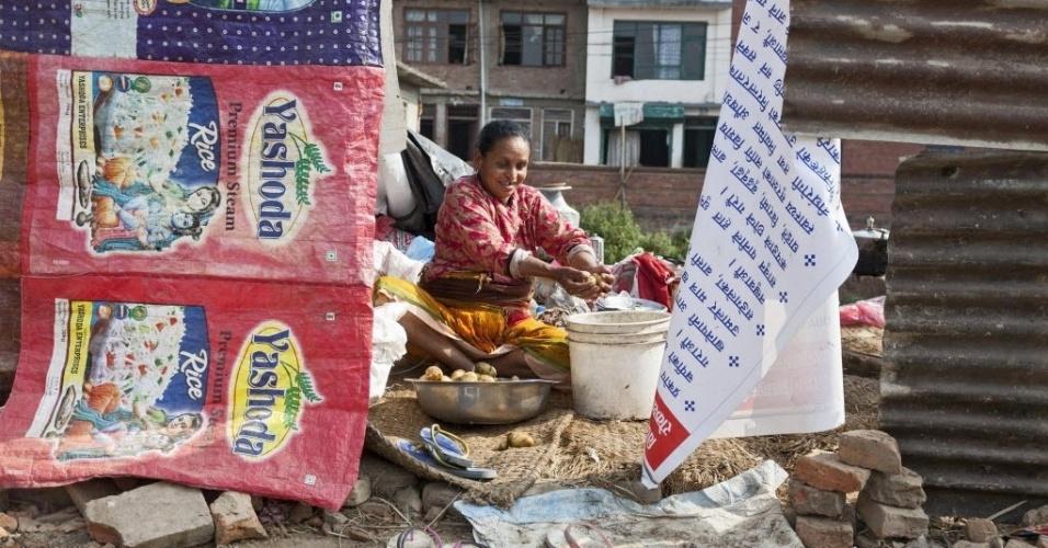 16.mai.2015 - Nepalesa lava batatas para fazer o almoço em um abrigo provisório na vila Harisiddi, nos arredores de Lalitpur. O novo sismo do dia 12 de maio deixou mortos e feridos